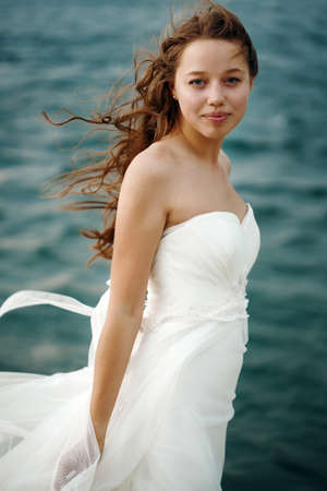 dress blowing in the wind: Beautiful Woman in White Dress Standing against Stormy Sea. Blowing Wind Hair. Looking to Camera. Selective Focus. Grain Added for Best Impression.