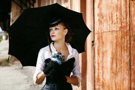 Portrait of Sexy Beautiful Woman in Historical Costume with Black Umbrella. Female Standing on the Abandoned Railway Station. Book Cover Concept. Banco de Imagens