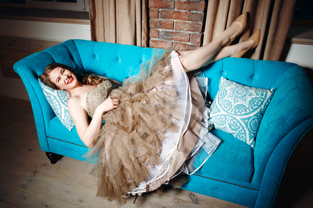 stage make up: Full Body Portrait of Beautiful Laughing Woman Lying on Blue Couch, in Luxury Green Dress with Stage Make Up. Loft Interior Indoors, Evening Time.