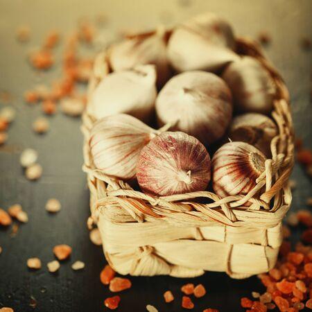 bulbet: Garlic Close Up in a Basket with Pink Himalayan Salt on Dark Background. Image Toned. Selective Focus.