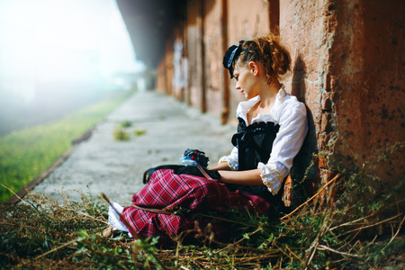 victorian girl: Beautiful Woman in Historical Garment Sitting on the Abandoned Railway Station. Space for Text. Book Cover Concept.