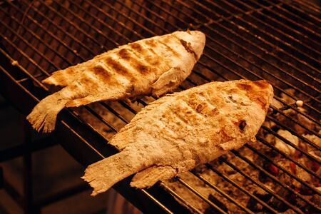 coal fish: Fish is Cooking on Grill Grid Close-up. Street Food in Thailand. Stock Photo