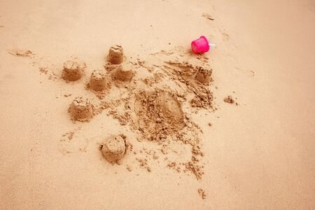 child's: Child`s Sand Castles on a Beach or in Sandbox with Little Pink Plastic Bucket Stock Photo