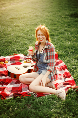 red plaid: Young Beautiful Smiling Woman Dressed in Pin Up Style Sitting on a Red Plaid on Green Grass in Summer Park. Picnic.