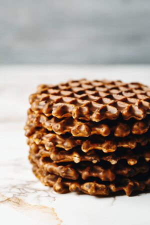 foodies: Stack of Homemade Belgian Waffles with Chocoltae Icing Close Up Side View on Grey Background. Selective Focus.