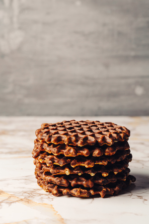 foodies: Stack of Homemade Belgian Waffles with Chocoltae Icing Close Up Side View on Grey Background. Selective Focus. Copy Space. Stock Photo