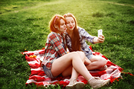 Two Young Hipster Girls Having Fun and Taking Photos (Making Selfie) on Smartphone at the Picnic in a Summer Park at the Sunset.