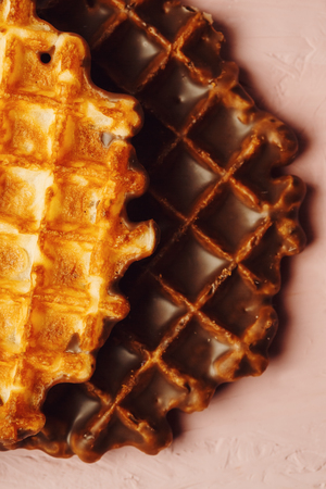 foodies: Round Belgian Waffles with Chocolate Icing Extreme Close-up on Pink Background. One Waffle with Icing, One without. Selective Focus, Great for Text.