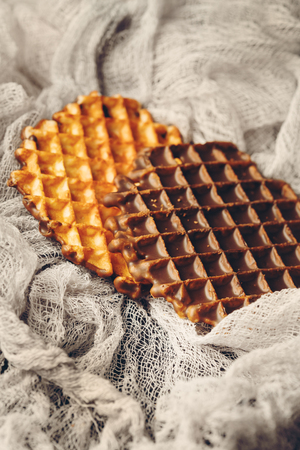 FOODIES: Round Belgian Waffles with Chocolate Icing Served on Fabric Close-up View, Selective Focus