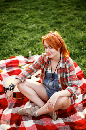 red plaid: Young Beautiful Smiling Woman Dressed in Pin Up Style Sitting on a Red Plaid on Green Grass in Summer Park