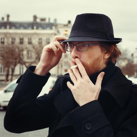hombre con barba: Atractivo hombre con barba que desgasta el sombrero de fumadores en la calle en la ciudad europea Foto de archivo