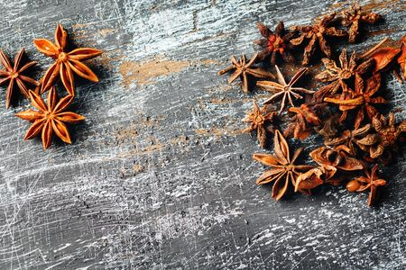 surface view: Food frame with heap of Star Anise on vintage black surface. View from above. Space for your text.
