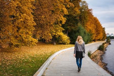 Volledig lichaam van vrouw die in de herfstpark loopt. Stedelijke parkscène. Dijk dichtbij rivier. Achteraanzicht.