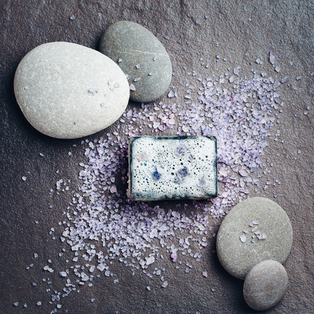 Spa and beauty treatment composition with soap, sea salt and massage stones on dark