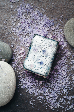 Harmony composition with soap, sea salt and massage stones on dark. Close-up. Imagens