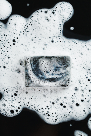 Black coal soap in foam on black background. Close-up composition. Top view.