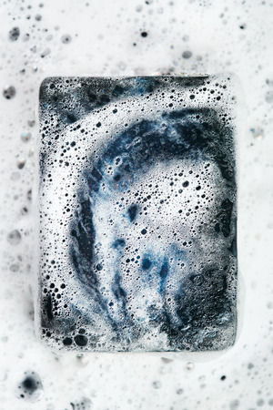 Close-up of black coal soap bar in foam. Top view. Imagens