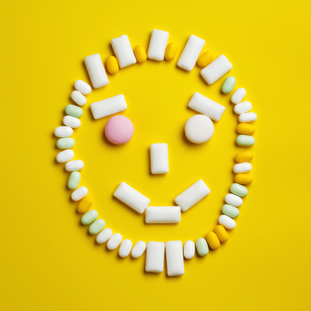 Funny round smily face made of different chewing gums, mint candies and drops on bright yellow background