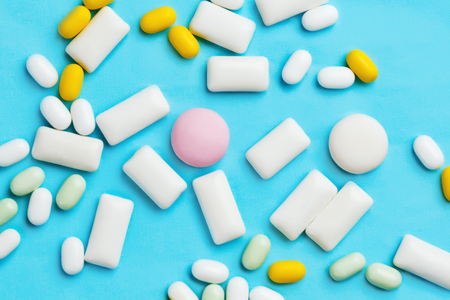 minty: Heap of different chewing gums, mint candies and drops on bright blue background Stock Photo