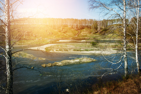 flood area: Landscape view of the river overflow among hills. Northern nature. Spring time. Selective focus. Lens flare. Stock Photo