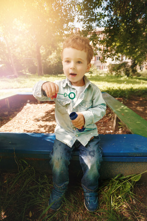 1 2 years: Cute little boy playing at the children playground outdoors with soap bubbles. Lens flare effect. Stock Photo