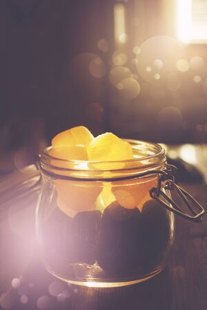 Mason jar full of jelly candies in sunset illuminated kitchen with bokeh light effect. Selective focus, image toned.