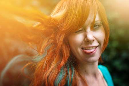 freaky: Young trendy freaky woman with colored bright red head having fun and showing tongue. Headshot with sunlight effect, summer mood outdoors.