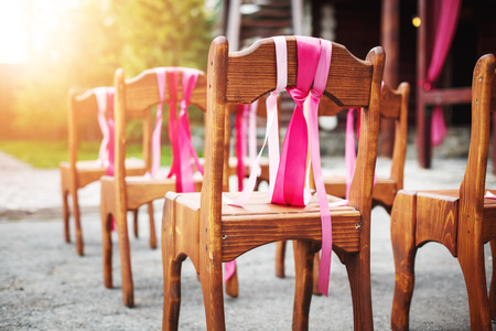Beautiful wooden chairs decorated with ribbons on wedding reception