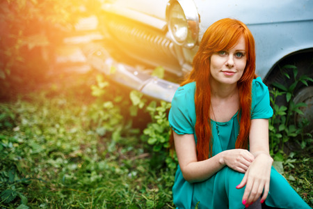 Funny bright young woman posing near vintage abandoned old car. Smiling and sitting in grass. Colored red long hair. Lens flare effect. Close up.