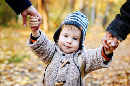 warm clothes: Cute smilimg kid in warm clothes  having fun and holding parents by hands