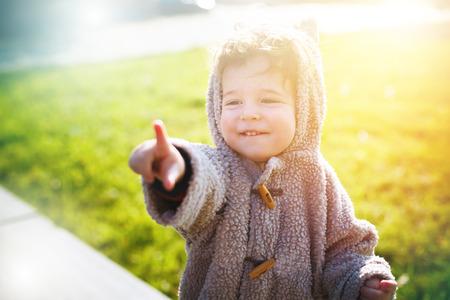 luz natural: Niño lindo en ropa divertida como la suite de oso de peluche sonriendo y riendo a la luz del sol