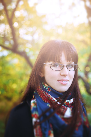 autumn young: Real woman in glasses at the nature. Blurred effect, selective focus.
