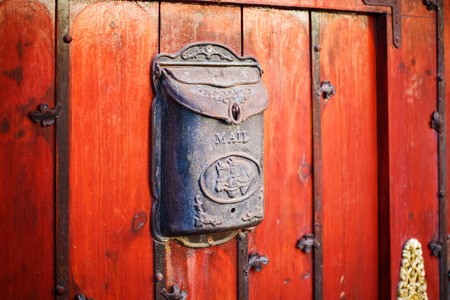 mail slot: Black vintage post box on rusty red wall