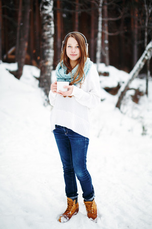 full height: Beautiful woman drinking hot drink in winter park. Winter holidays concept. Full height, looking at camera. Winter landscape on the background.