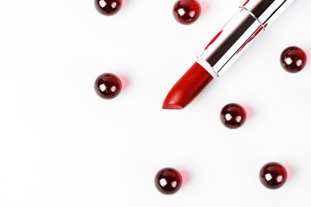 periods: Delicate concept of female life, beauty and menstruation periods. Red lipstick with red marble drops over white background. Protection and safety. Top view, close up.