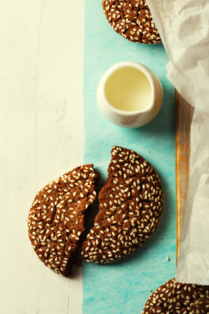 Chocolate oat cookies with sesame on top for healthy breakfast, top view, image toned
