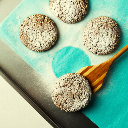 oven tray: Fresh baked chocolate cookies in sugar powder on oven tray, top view