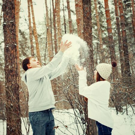 winter vacation: Young loving couple having fun in winter forest, winter vacation concept, toned