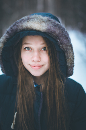 warm clothes: Headshot of young beautiful woman in warm clothes and hood in wintertime. Woman smiling.