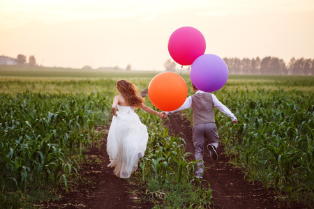 Wedding couple running away on the field with big bright colored balloons, full body