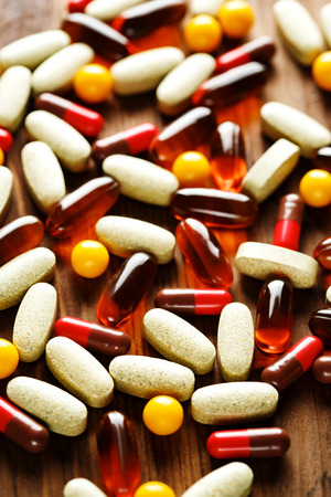 Organic dietary treatment, vitamin capsules on wooden background, selective focus Stock Photo