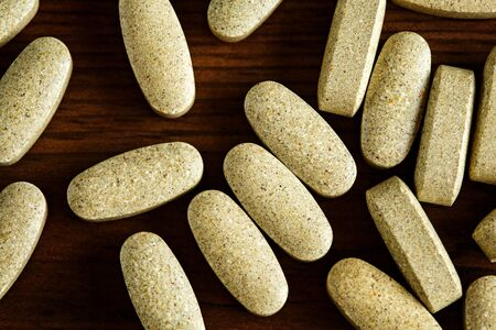 Organic dietary treatment, vitamin capsules on wooden background, flat lay, close-up