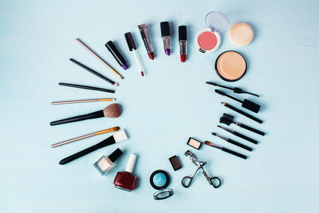 expended: Various make-up products expended as round on blue background. Cosmetics background with copy space.