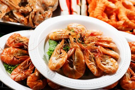 plates of food: Street food market outdoors, shrimp portions on plastic plates Stock Photo