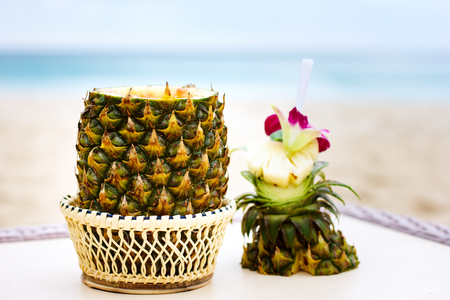 colada: Exotic cocktail, pina colada in an open pineapple at the beach