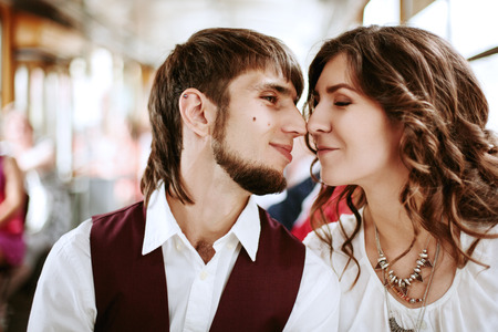 transportaion: Young hipster couple kissing in the bus, blurred background Stock Photo