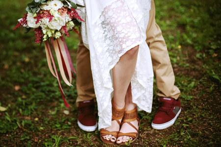 Boho chic style. Legs of wedding couple close-up, freedom concept.