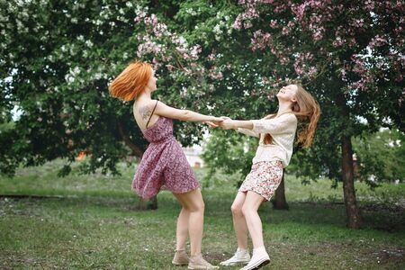 Two young beautiful girls having fun in spring park