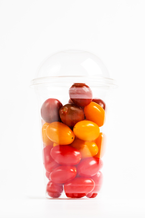 Cherry tomatoes in transparent plastic container on white background, close-up