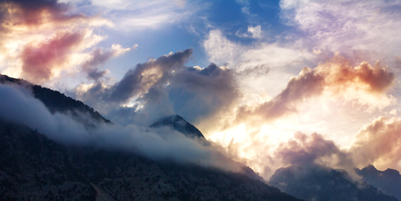Breathtaking awesome mountain landscape with tops in clouds at sunset Zdjęcie Seryjne
